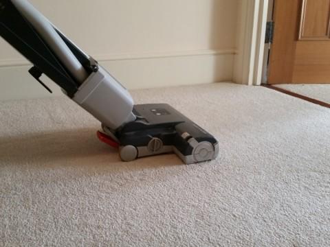 grey upright vacuum cleaner on cream carpet